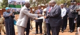 HISTORIC MOMENT: The Minister of Internal Affairs, Gen. Aronda Nyakairima (L), handing over the land title for the site of the JLOS House Complex to the Minister of Justice and Constitutional Affairs, Gen. Kahinda Otafiire at Naguru, Kampala on September 19 2013. (PHOTO: JLOS Media)